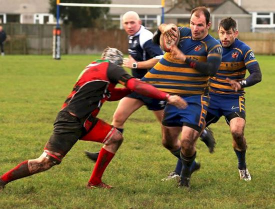 The Llantwit defender grabs hold of Stuart Clarke's shirt as he makes ground